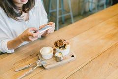 Muchacha asiática que toma la foto de la torta, del helado, y de la leche de la tostada del chocolate en la cafetería Afición de  Imagenes de archivo