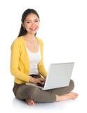 Muchacha asiática que usa el ordenador portátil Foto de archivo libre de regalías