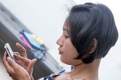 Muchacha asiática que usa un teléfono elegante Imagenes de archivo