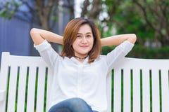 Muchacha asiática relajar sentarse en la sonrisa despreocupada de la felicidad del parque fotos de archivo