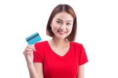 Muchacha asiática sonriente amistosa hermosa que muestra la tarjeta de crédito en Han Foto de archivo