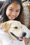 Muchacha asiática sonriente con su perro de animal doméstico Fotos de archivo