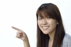 Muchacha asiática sonriente que señala a la izquierda Fotografía de archivo libre de regalías