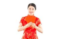 Muchacha asiática sonriente que sostiene sobres rojos Foto de archivo
