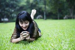 Muchacha asiática sonriente que usa un teléfono Fotos de archivo libres de regalías