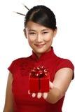Muchacha asiática tradicional que muestra un regalo de la Navidad Fotografía de archivo