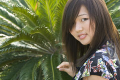 Muchacha asiática triguena con la palma verde Fotografía de archivo