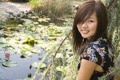 Muchacha asiática triguena que se sienta en la orilla del lago. Fotos de archivo libres de regalías