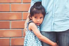 Muchacha asiática triste del niño que abraza su pierna de la madre Imagenes de archivo