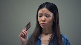 Muchacha asiática triste que sueña sobre el chocolate dulce que guarda la dieta, nutrición sana metrajes