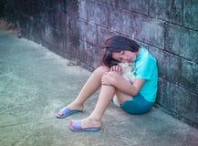 Muchacha asiática triste y preciosa contra fondo de la pared del grunge Foto de archivo libre de regalías