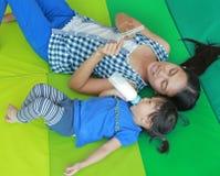 Muchacha asiática y madre del niño que mienten en el colchón y que juegan la tarjeta flash para Brain Development adecuado en la  Imagenes de archivo