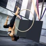 Muchacha asi?tica del gimnasta que cuelga en aro a?reo fotos de archivo libres de regalías