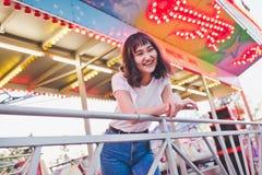 Muchacha asi?tica hermosa en un parque de atracciones, sonriendo foto de archivo