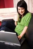 Muchacha asiática con la taza de la computadora portátil y de café Imagenes de archivo