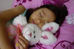 Muchacha asiática durmiente que detiene a su Toy Rabbit. Fotografía de archivo