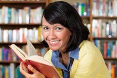 Muchacha asiática en biblioteca que lee un libro Imagenes de archivo