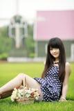 Muchacha asiática joven en el césped Fotos de archivo