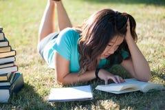 Muchacha asiática joven que estudia afuera Imagenes de archivo