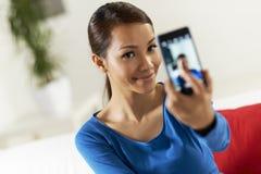 Muchacha asiática que comparte la red del social del pictureon Fotografía de archivo