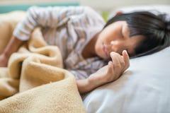 Muchacha asiática que duerme en la cama cubierta con la manta Fotos de archivo libres de regalías