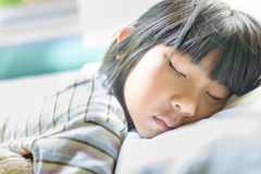 Muchacha asiática que duerme en la cama cubierta con la manta Imagen de archivo
