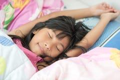 Muchacha asiática que duerme en la cama cubierta con la manta Fotografía de archivo