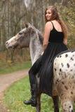 Muchacha asombrosa con el pelo largo que monta un caballo Foto de archivo libre de regalías