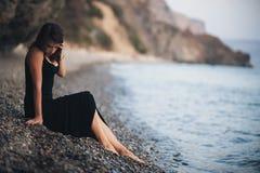 Muchacha asombrosa en el vestido negro que se sienta en la orilla de la playa Fotografía de archivo libre de regalías