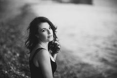Muchacha asombrosa en el vestido negro que se sienta en la orilla de la playa Fotos de archivo libres de regalías
