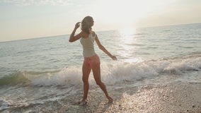 Muchacha asombrosa que corre a lo largo de la playa, en un mojado almacen de video