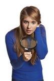 Mujer sorprendida que mira a través de la lupa hacia abajo Fotos de archivo libres de regalías