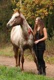 Muchacha asombrosa que se coloca al lado del caballo del appaloosa Imagen de archivo