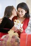 Muchacha asombrosamente su madre con el regalo de la Navidad Imagen de archivo