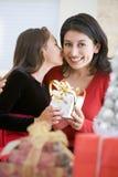 Muchacha asombrosamente su madre con el regalo de la Navidad Imagenes de archivo