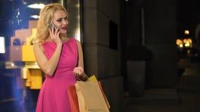 Muchacha astuta que liga con su novio en el teléfono, pidiendo el dinero nuevo vestido almacen de metraje de vídeo