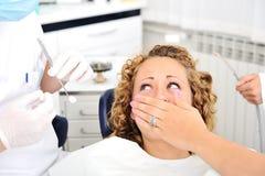 Muchacha asustada en el chequeo de los dientes del dentista Fotos de archivo libres de regalías