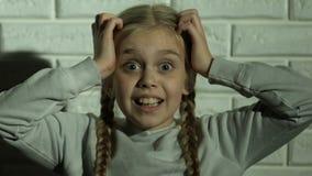 Muchacha asustada que grita llevando a cabo la cabeza con las manos, trauma psicológico, pesadilla almacen de metraje de vídeo