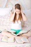 Muchacha asustada que lee un libro en cama Fotografía de archivo