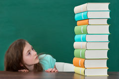 Muchacha asustada que mira los libros coloridos Fotografía de archivo