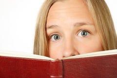 Muchacha asustada que mira sobre el libro Fotos de archivo libres de regalías