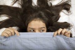 Muchacha asustada que oculta en cama Fotos de archivo libres de regalías