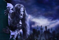 Muchacha asustadiza del zombi de los Undead en el cementerio de Halloween fotos de archivo