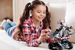 Muchacha atenta que mira hacia abajo su juguete imagen de archivo