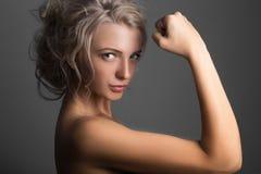 Muchacha atlética atractiva que muestra el bíceps Imágenes de archivo libres de regalías