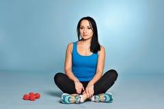Muchacha atlética con el cuerpo del músculo que se sienta en piso Imagen de archivo