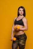 Muchacha atlética con pesas de gimnasia Foto de archivo libre de regalías