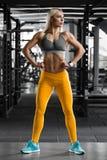 Muchacha atlética en el gimnasio, resolviéndose Mujer de la aptitud que muestra el ABS y el vientre plano, cuerpo formado Fotografía de archivo