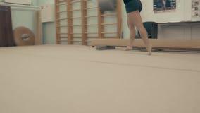 Muchacha atlética en gimnasio, corriendo alrededor en los círculos, haciendo calentamiento antes de entrenar, primer metrajes