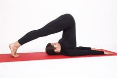 Muchacha atlética hermosa en el traje negro que hace yoga asana del halasana - actitud de la paleta Aislado en el fondo blanco imagenes de archivo